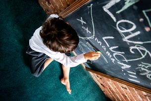 Boy in school uniform writing on blackboard at homeの写真素材 [FYI03623754]