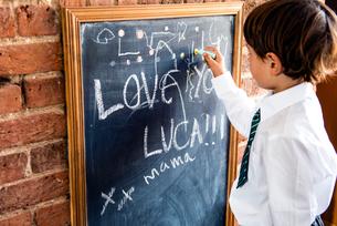 Boy in school uniform writing on blackboard at homeの写真素材 [FYI03623756]