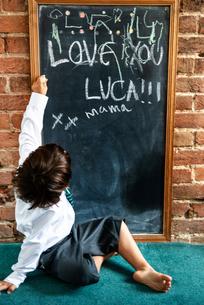 Boy in school uniform writing on blackboard at homeの写真素材 [FYI03623757]