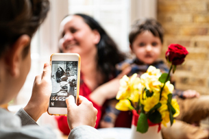 Boy taking smartphone photo mother and toddler brother celebrating mothers day, over shoulder viewの写真素材 [FYI03623760]