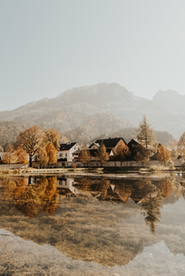 Traditional houses on lakeside below misty mountain landscape, Admont, Styria, Austriaの写真素材 [FYI03623807]