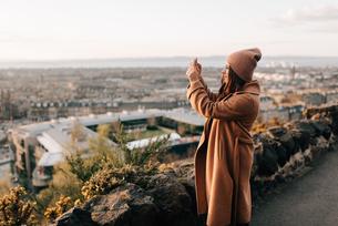 Woman taking photo from Calton Hill, Edinburgh, Scotlandの写真素材 [FYI03623819]