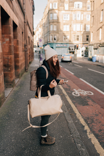 Woman waiting on kerb with cellphone and luggage, Edinburgh, Scotlandの写真素材 [FYI03623822]