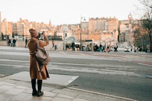 Woman sightseeing and taking photo, Calton Hill, Edinburgh, Scotlandの写真素材 [FYI03623826]