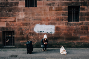 Woman texting on kerb with cellphone and luggage, Edinburgh, Scotlandの写真素材 [FYI03623828]