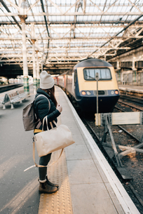 Woman waiting on platform in train station, Edinburgh, Scotlandの写真素材 [FYI03623829]