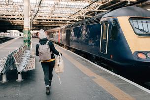 Woman walking to train at platform, Edinburgh, Scotlandの写真素材 [FYI03623830]