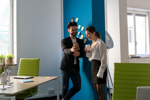 Male and female business creatives taking a break and looking at smartphone in officeの写真素材 [FYI03623875]