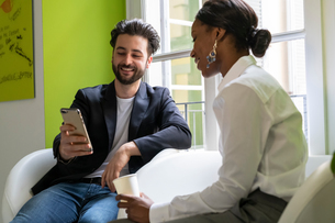 Two male and female business creatives looking at smartphone in officeの写真素材 [FYI03623880]
