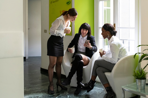 Three female business creatives taking a break and looking at smartphone in officeの写真素材 [FYI03623882]