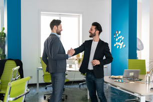 Two male business creatives smiling and shaking hands in officeの写真素材 [FYI03623885]