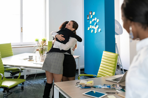 Two female business creatives hugging in office, over shoulder viewの写真素材 [FYI03623890]