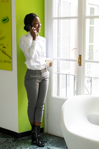 Young female business creative making smartphone call in officeの写真素材 [FYI03623895]