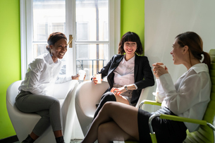 Young female business creative team taking a break in office armchairsの写真素材 [FYI03623899]