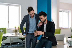 Young male business creatives looking at smartphone in open plan officeの写真素材 [FYI03623901]