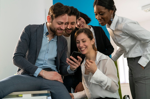 Young female and male business creative team looking at smartphone in officeの写真素材 [FYI03623906]