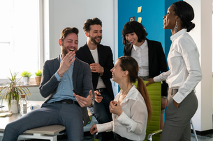 Young female and male business creative team laughing in officeの写真素材 [FYI03623907]