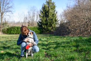 Woman taking pet dog for walk in parkの写真素材 [FYI03623915]