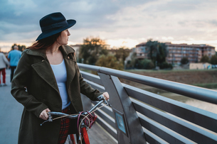 Young woman with bicycle looking out from footbridge at dusk, Florence, Tuscany, Italyの写真素材 [FYI03624027]