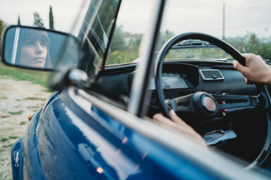 Mirror image of woman driving carの写真素材 [FYI03624105]