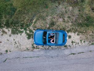 Overhead view of friends talking inside car by roadsideの写真素材 [FYI03624109]