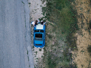 Overhead view of friends reading route map on car bonnet by roadsideの写真素材 [FYI03624111]