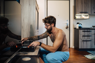 Mid adult man with tattoos playing vinyl on turntableの写真素材 [FYI03624134]