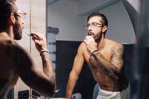 Mid adult man with tattoos brushing teeth at bathroom mirrorの写真素材 [FYI03624158]