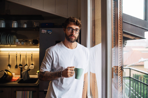 Mid adult man with coffee by apartment window, portraitの写真素材 [FYI03624171]