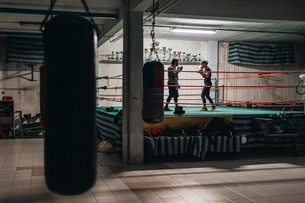 Boxer sparring with trainer in boxing ringの写真素材 [FYI03624330]
