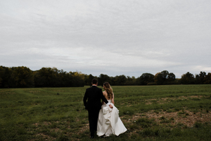 Romantic young groom carrying bride's wedding dress train in field, rear viewの写真素材 [FYI03624355]