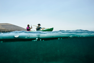 Teenage boy and mother sea kayaking, surface level side view, Limnos, Khios, Greeceの写真素材 [FYI03624365]