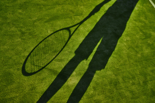 Cropped shadow of tennis player with tennis racket on green lawnの写真素材 [FYI03624374]
