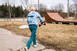 Blond boy carrying skateboard toward rural skateboard ramp, rear viewの写真素材 [FYI03624395]