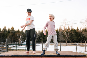 Boy and sister dancing on top of rural concrete slabの写真素材 [FYI03624402]