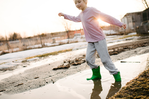 Boy playing in rural meltwater puddleの写真素材 [FYI03624410]