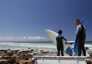 Boy surfer and father preparing surfboards on back of truck on beach, Cape Town, Western Cape, Southの写真素材 [FYI03624421]