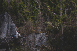 Climber bouldering in forest, Squamish, Canadaの写真素材 [FYI03624558]