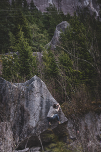 Climber bouldering in forest, Squamish, Canadaの写真素材 [FYI03624559]