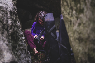 Climber putting on shoes between rocks, Squamish, Canadaの写真素材 [FYI03624565]