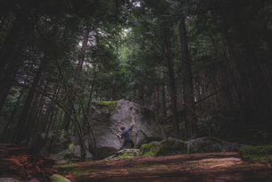 Climber bouldering in forest, Squamish, Canadaの写真素材 [FYI03624566]