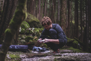 Climber taping fingers before bouldering in forest, Squamish, Canadaの写真素材 [FYI03624567]