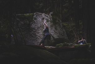 Climber bouldering, watched by friend, Squamish, Canadaの写真素材 [FYI03624569]