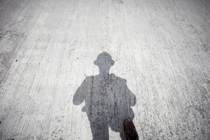 Construction worker's shadow on grey concrete slab, personal perspectiveの写真素材 [FYI03624602]