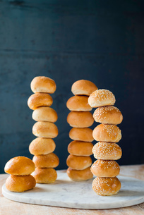 Large group of stacked white bread rolls on cutting boardの写真素材 [FYI03624615]