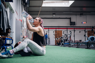Young woman drinking water in gymの写真素材 [FYI03624654]