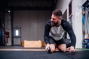 Young man kneeling on rubber flooring in gymの写真素材 [FYI03624739]