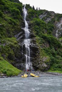 Group of adventure tourists looking at mountain waterfall on river bank, Valdez, Alaska, USAの写真素材 [FYI03624743]