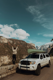 Young woman on top of roadside wall with hands raised, rear view, Yosemite Village, California, USAの写真素材 [FYI03624805]