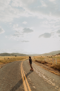 Young barefoot male skateboarder skateboarding on rural road, rear view, Exeter, California, USAの写真素材 [FYI03624834]